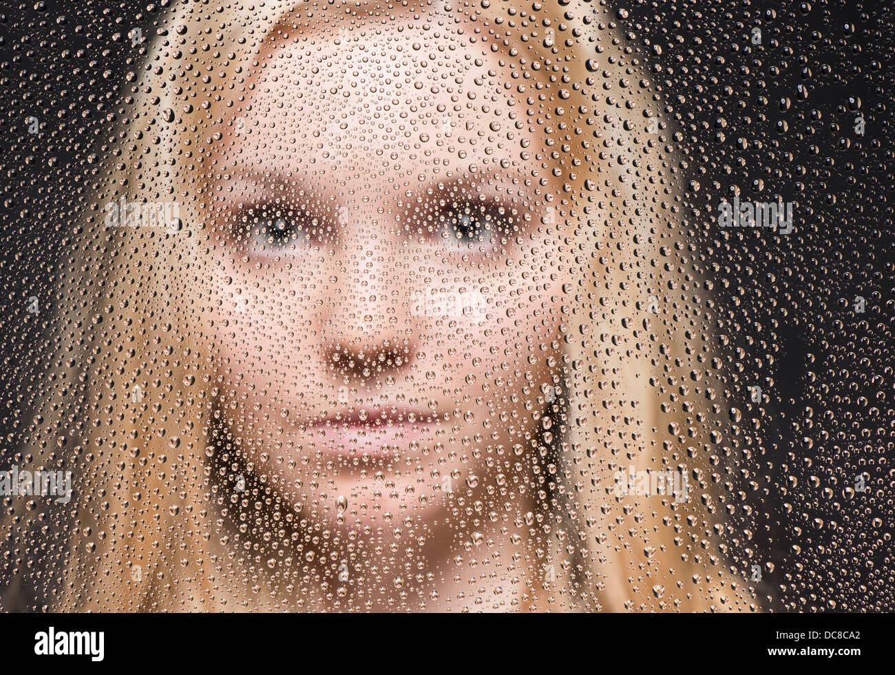 Portrait of young blond female teenager looking out of window covered with raindrops Stock Photo