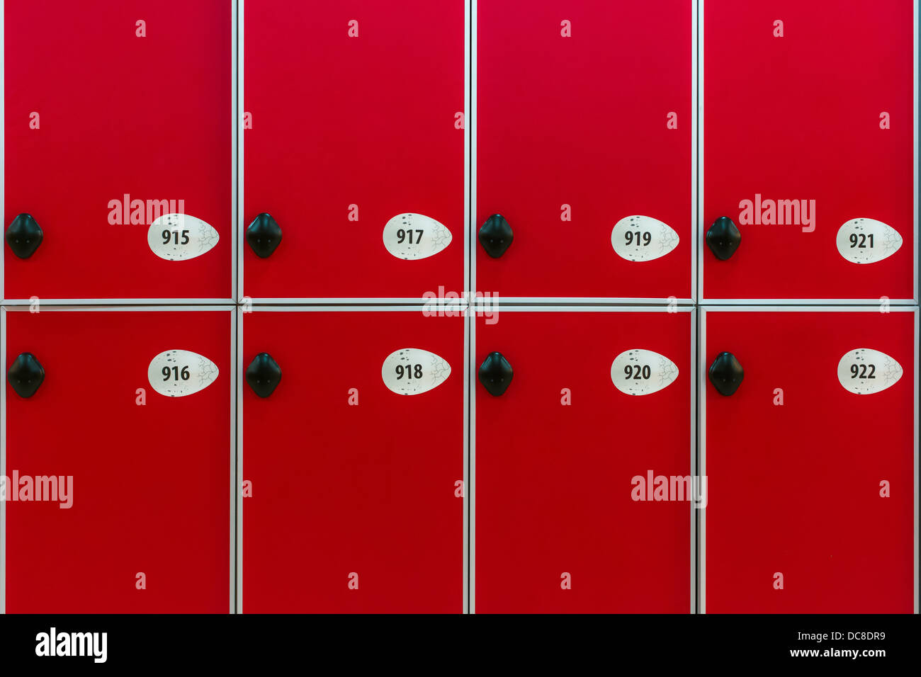 Red doors with numbers and locks in the locker room - Stock Image