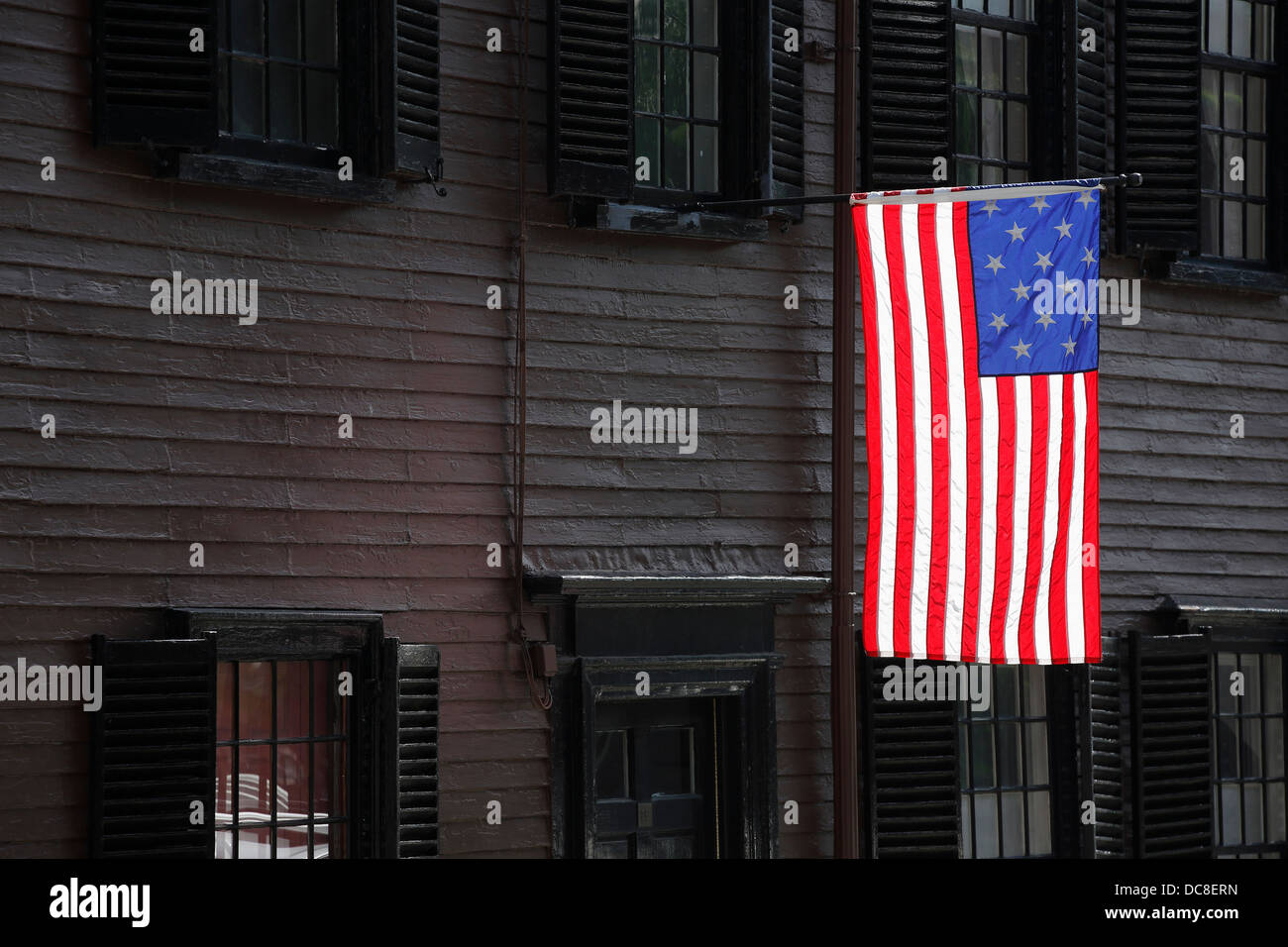 A 15 star flag flying in front of a colonial era house in the Charlestown neighborhood of Boston, Massachusetts - Stock Image