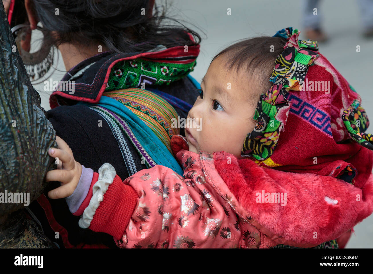 A young mother carrying her baby in Sapa, Vietnam, Asia. - Stock Image