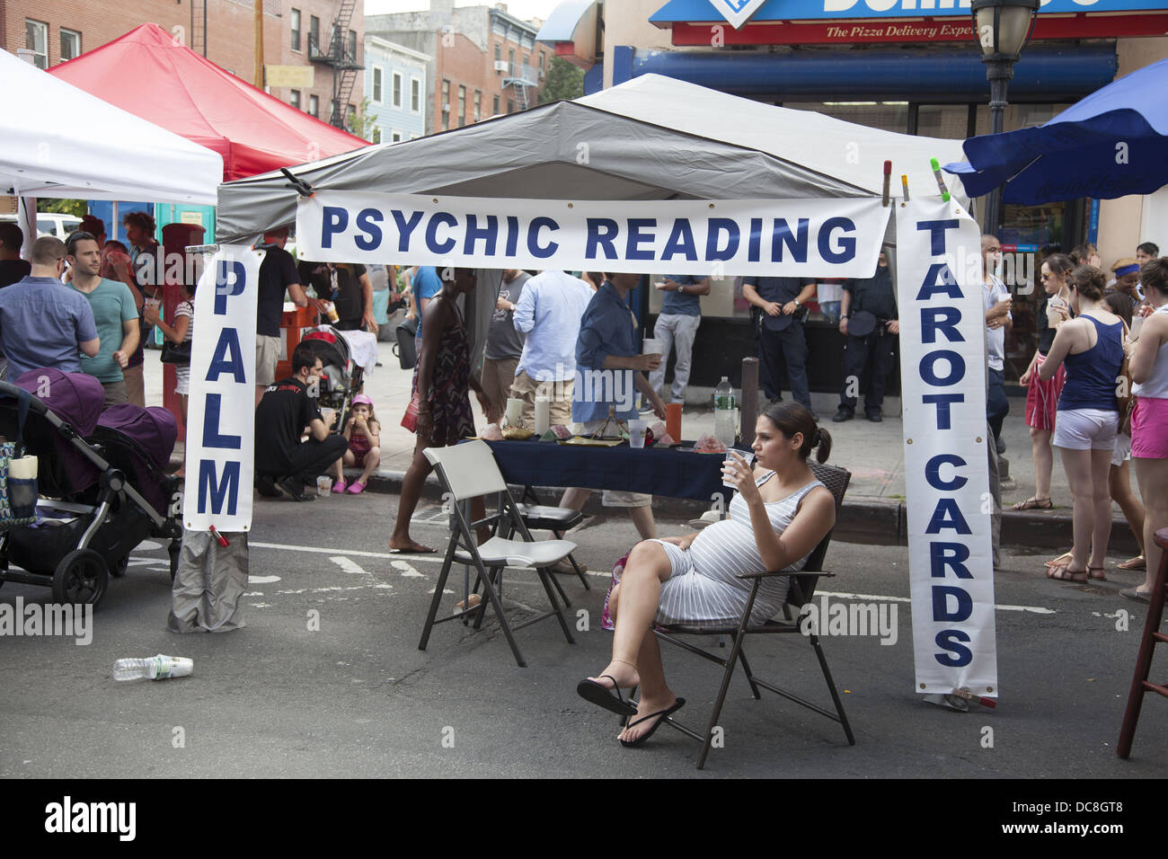 Psychic plies her craft at a Bastille Day street festival in Brooklyn, NY. - Stock Image