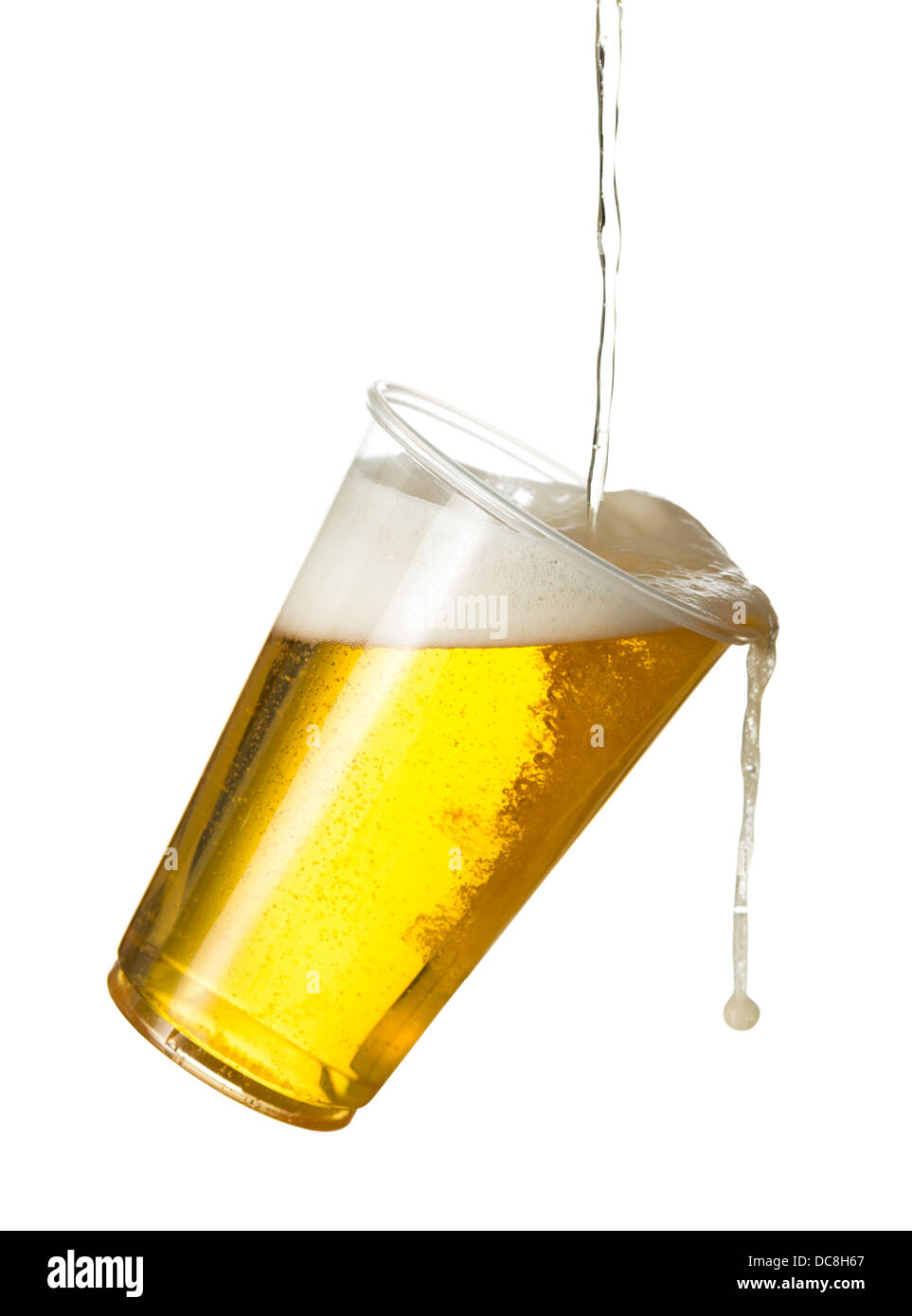 Pouring lager beer into a plastic disposable pint glass - spilling out / over - Stock Image