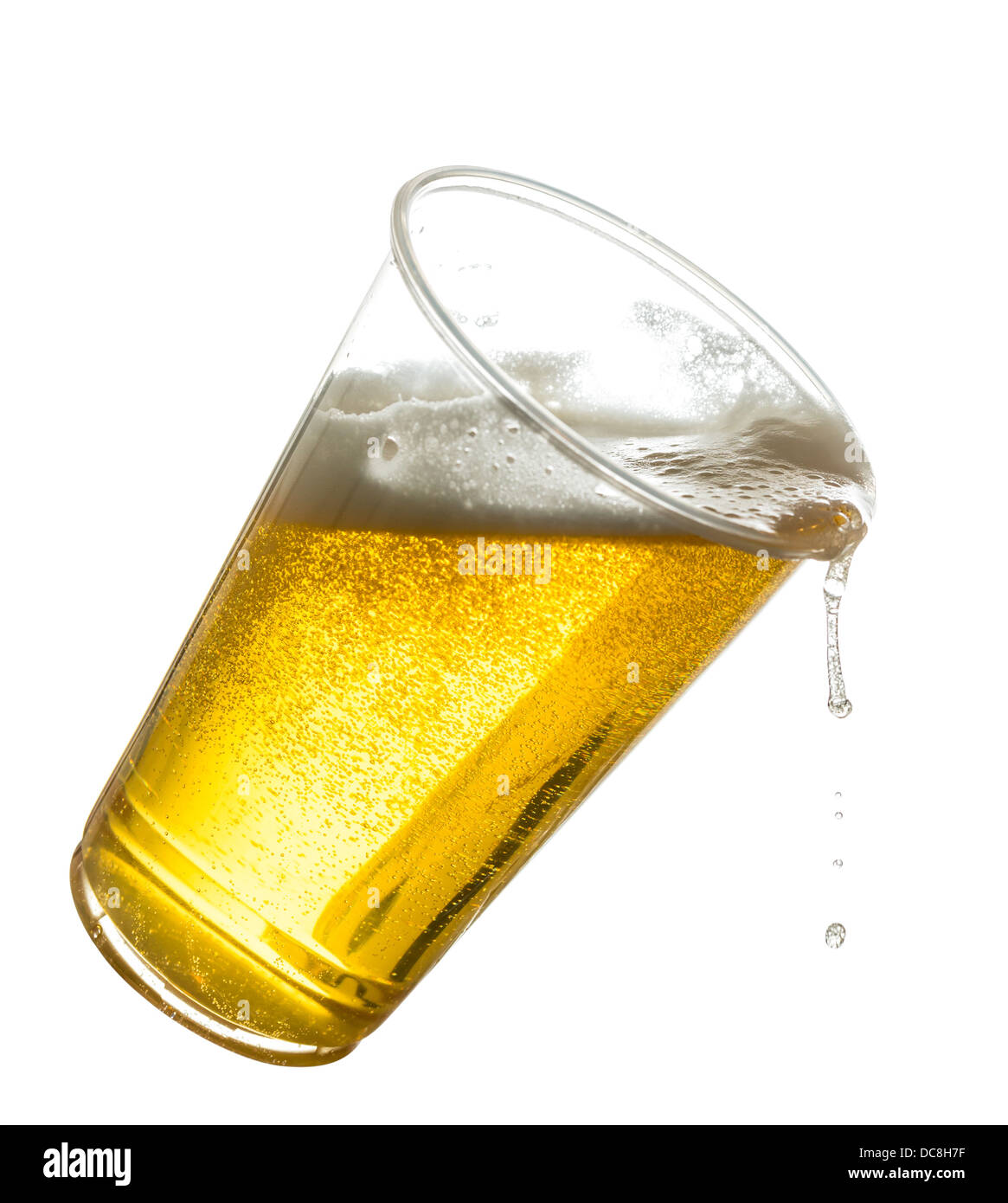 Beer / lager in a tilting plastic disposable pint glass spilling over - Stock Image