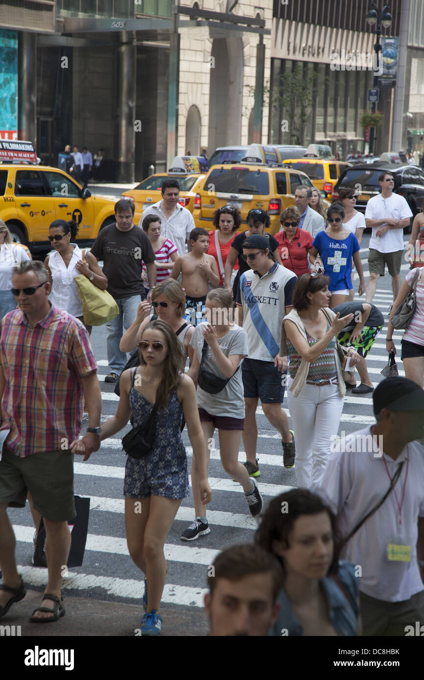 People croos the street at the always crowded intersection of 5th Avenue & 42nd Street, New York City. - Stock Image