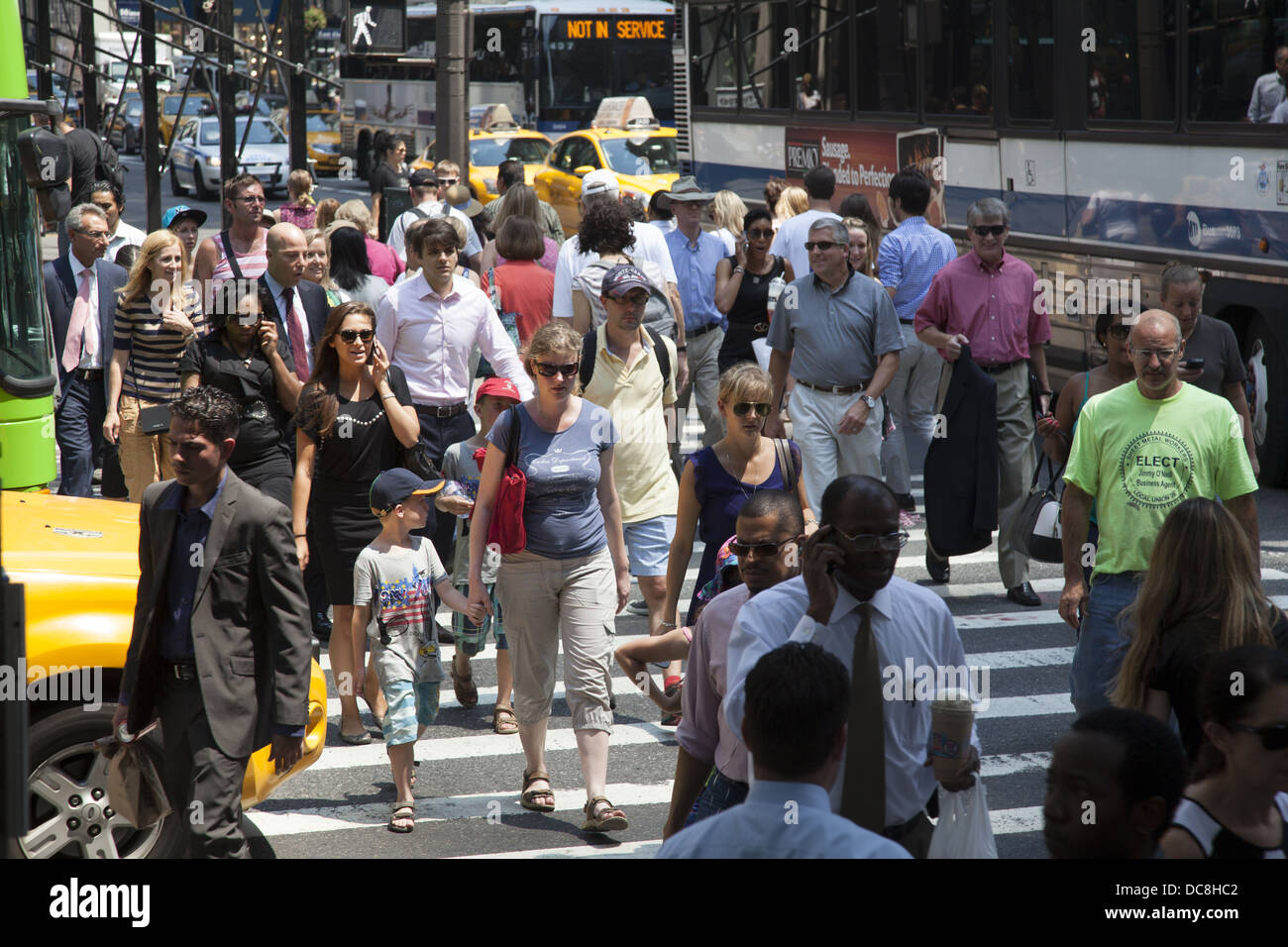 People cross the street at the always crowded intersection of 5th Avenue & 42nd Street, New York City. - Stock Image