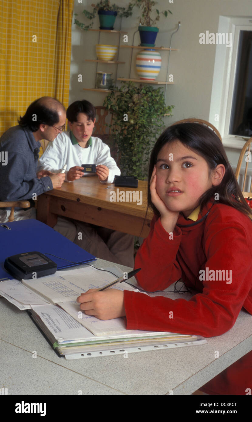 pensive girl at home doing homework while her father & son in background talk about his medical condition - Stock Image