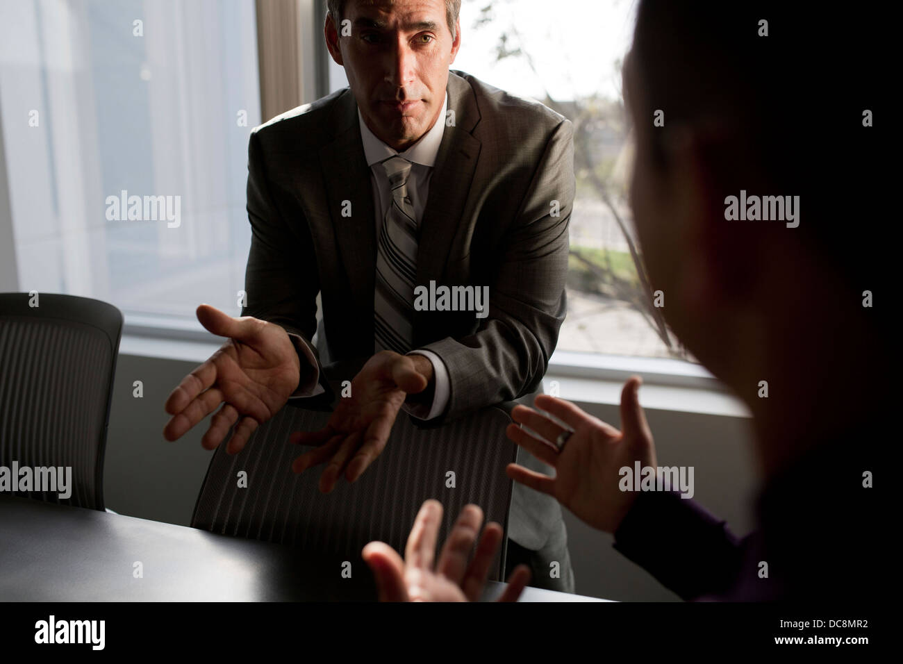 Two businessmen talking in a meeting room. - Stock Image