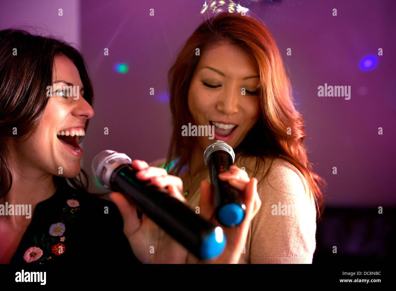 Two women singing karaoke. Stock Photo