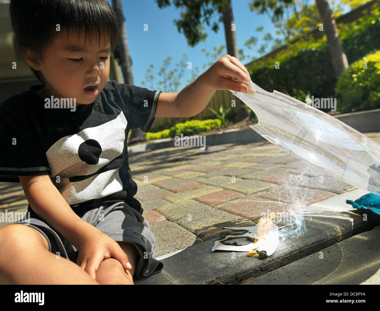Kid making fire with a magnifying glass. - Stock Image