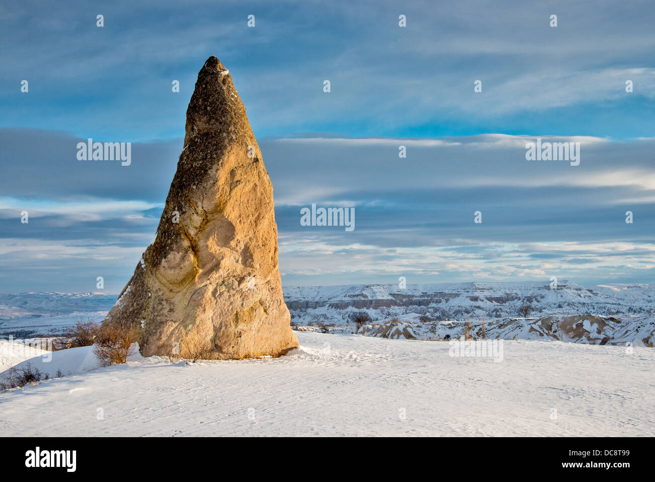 Pointy rock on top of a snowy mountain - Stock Image