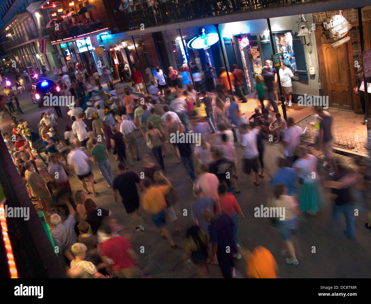 CROWD FOLLOWING MARCHING JAZZ GROUP BOURBON STREET FRENCH QUARTER DOWNTOWN NEW ORLEANS LOUISIANA USA - Stock Image