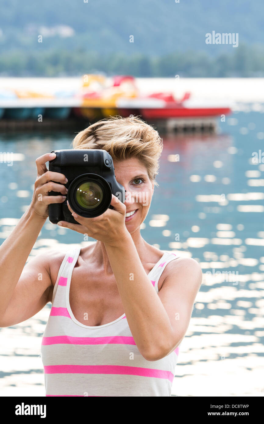 Young woman W34 on vacation takes a picture with her DSLR - Stock Image