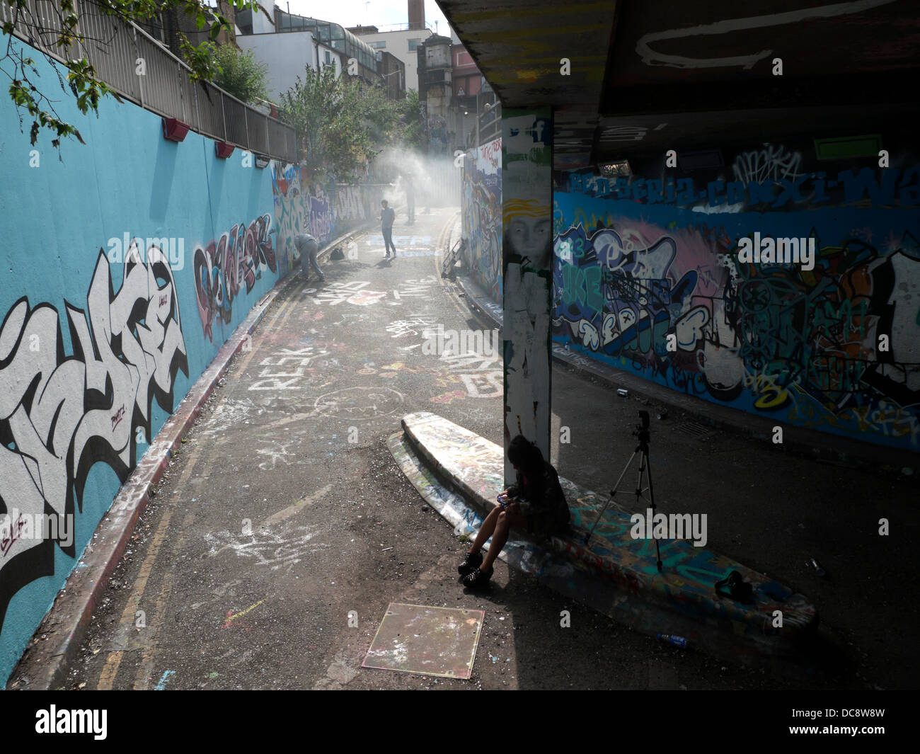 Artists spray painting with cans in the Leake Street Grafitti Tunnel, Lambeth London England UK - Stock Image
