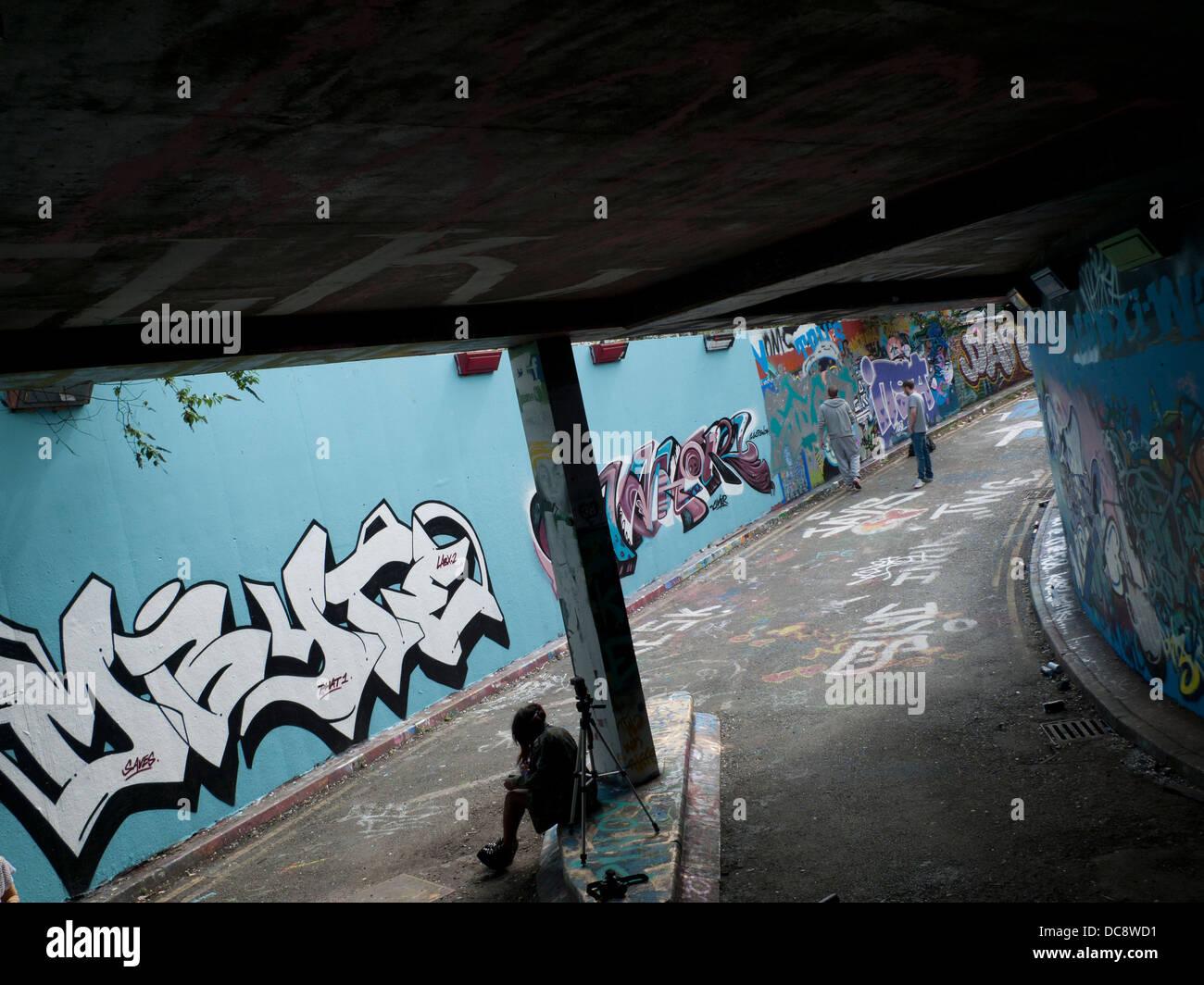 Artists working on wall in Leake Street Grafitti Tunnel, Lambeth London England UK - Stock Image
