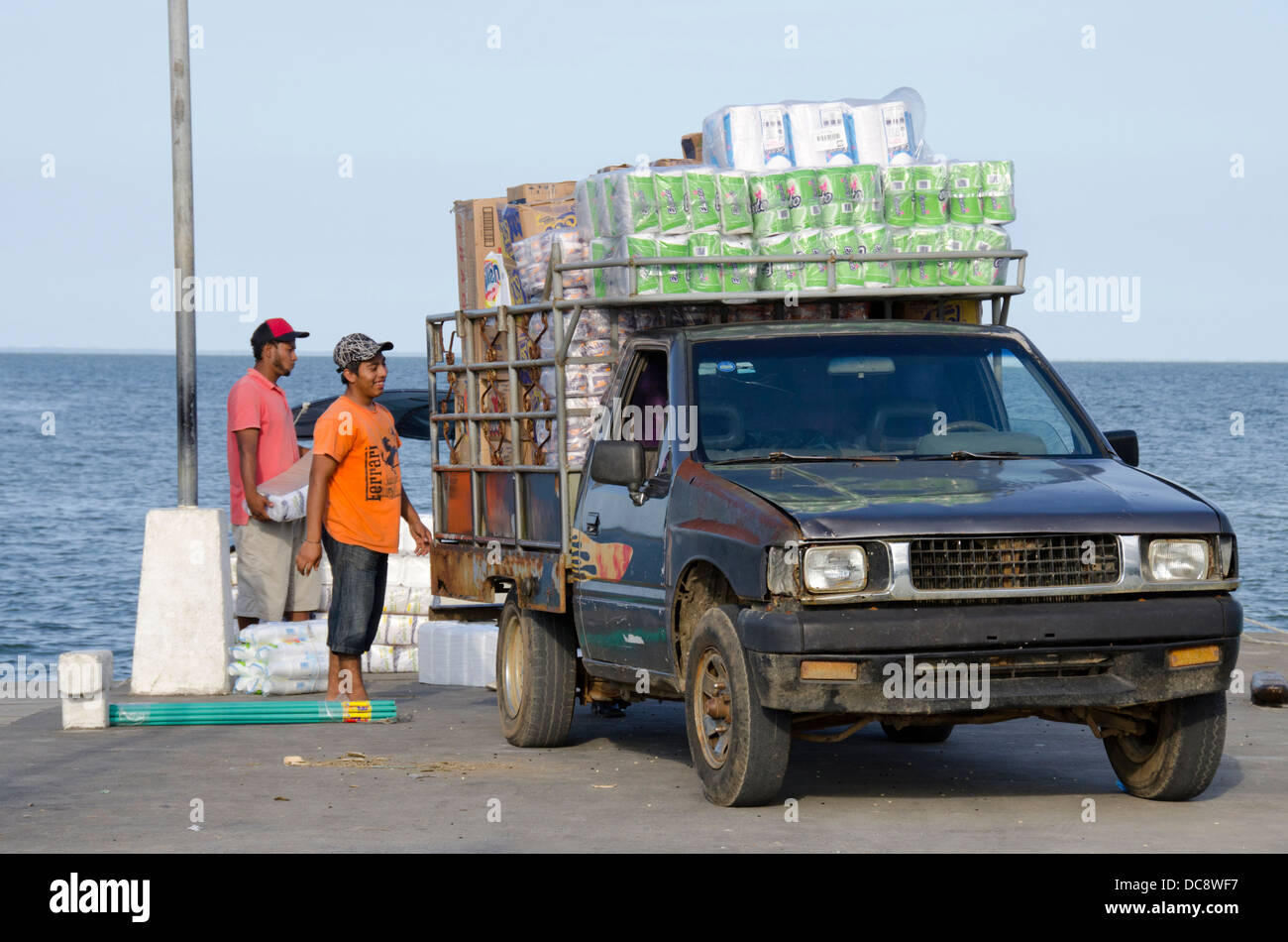 Guatemala, Livingston. Typical port pier with locals loading supplies into truck to take to the highlands. - Stock Image