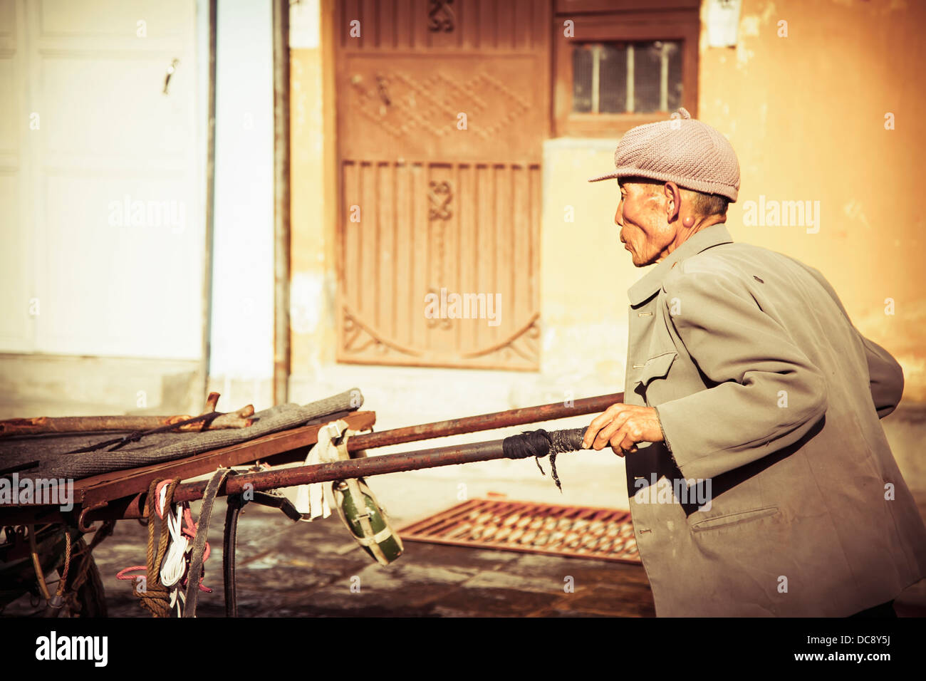 Old man pushes cart; Dali City, Yunnan Province, China - Stock Image