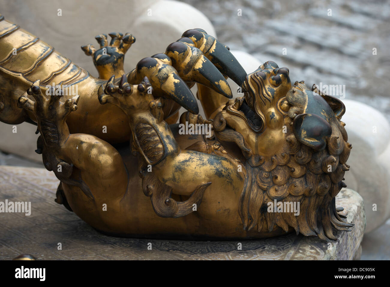 A gold and black sculpture depicting a claw attacking a smaller animal; Beijing, China - Stock Image