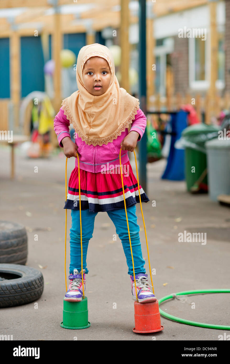 The St. Pauls Nursery School and Children's Centre, Bristol UK  - A Somali girl playing on stilts in the playground. - Stock Image