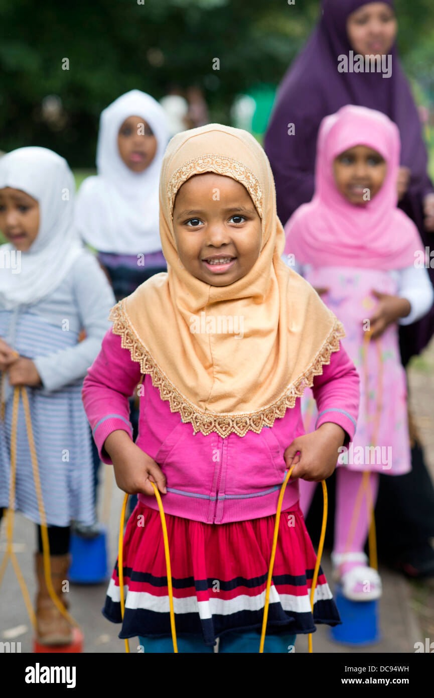 The St. Pauls Nursery School and Children's Centre, Bristol UK  - Somali girls playing on stilts in the playground. - Stock Image
