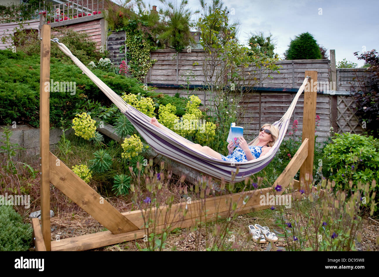 Attractive Caucasian woman in hammock in garden relaxing reading a book - Stock Image