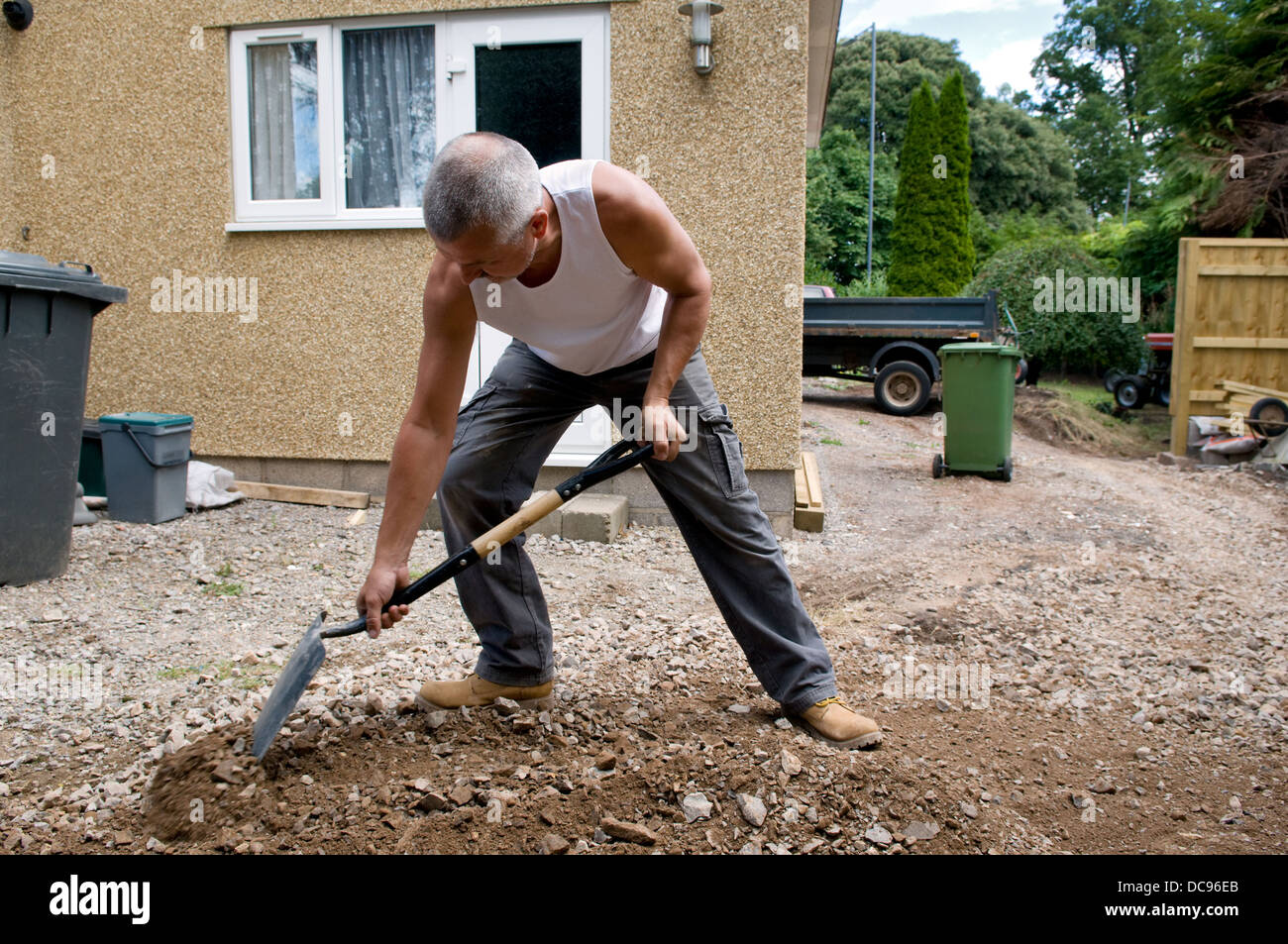 Caucasian man spreading and digging hardcore gravel in garden at home - Stock Image