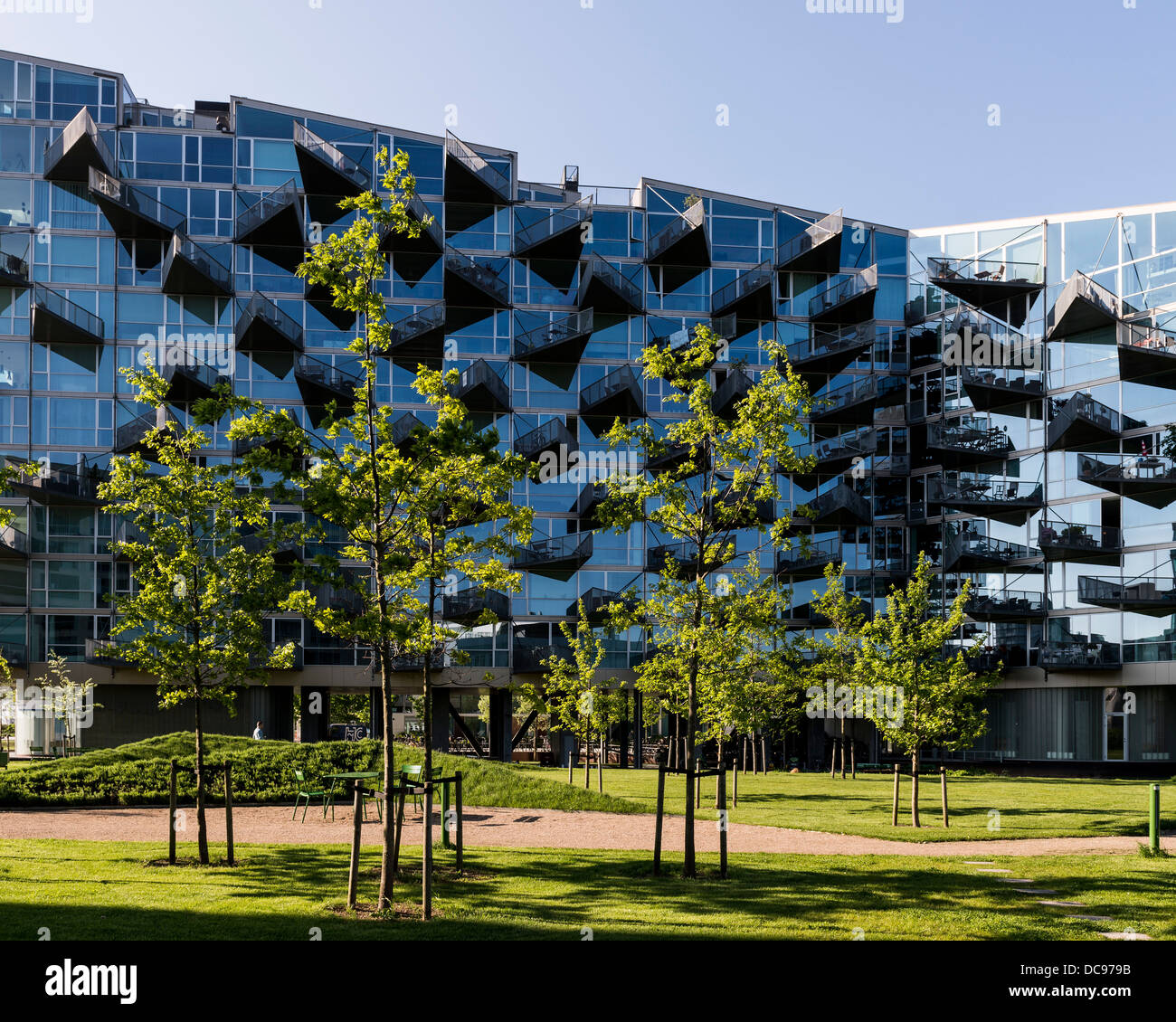 VM Houses, Copenhagen, Denmark. Architect: PLOT, 2013. View of building with trees and grass in foreground. Stock Photo