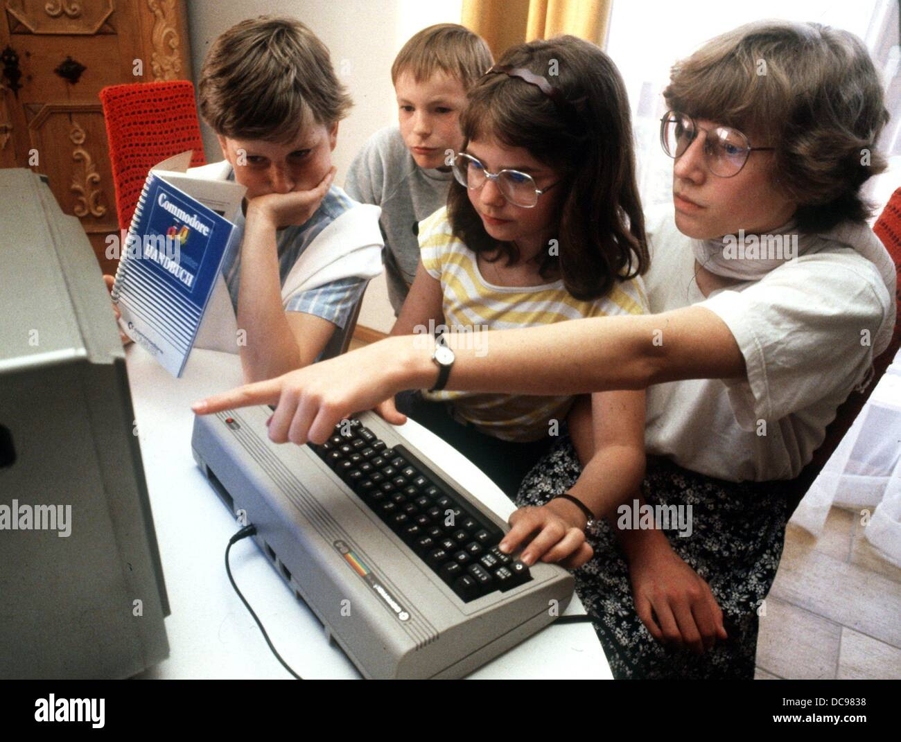 Adolescents try out a Commodore 64 in Nuremberg in May 1985. Stock Photo