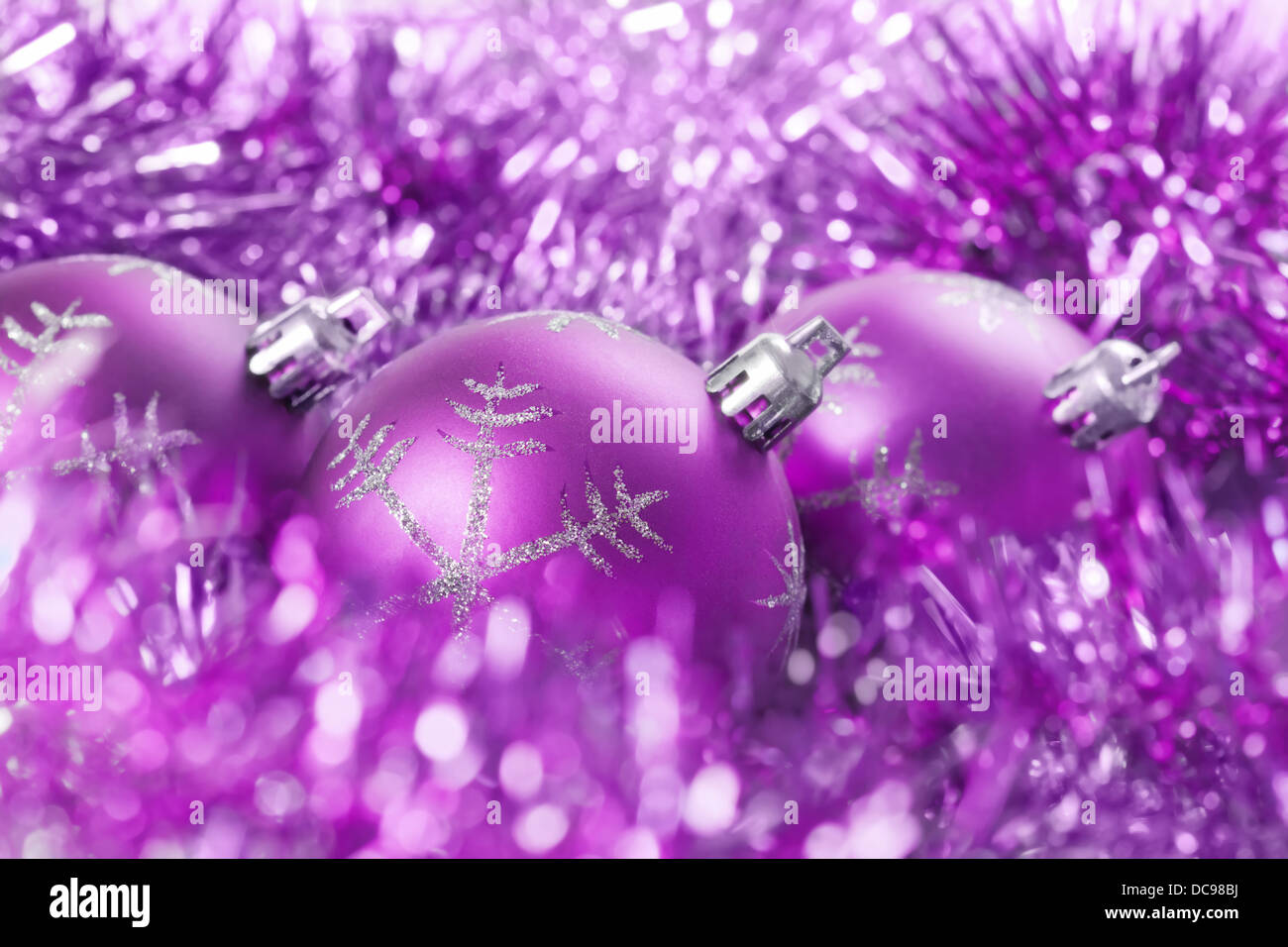 background from violet christmas balls with tinsel - Stock Image