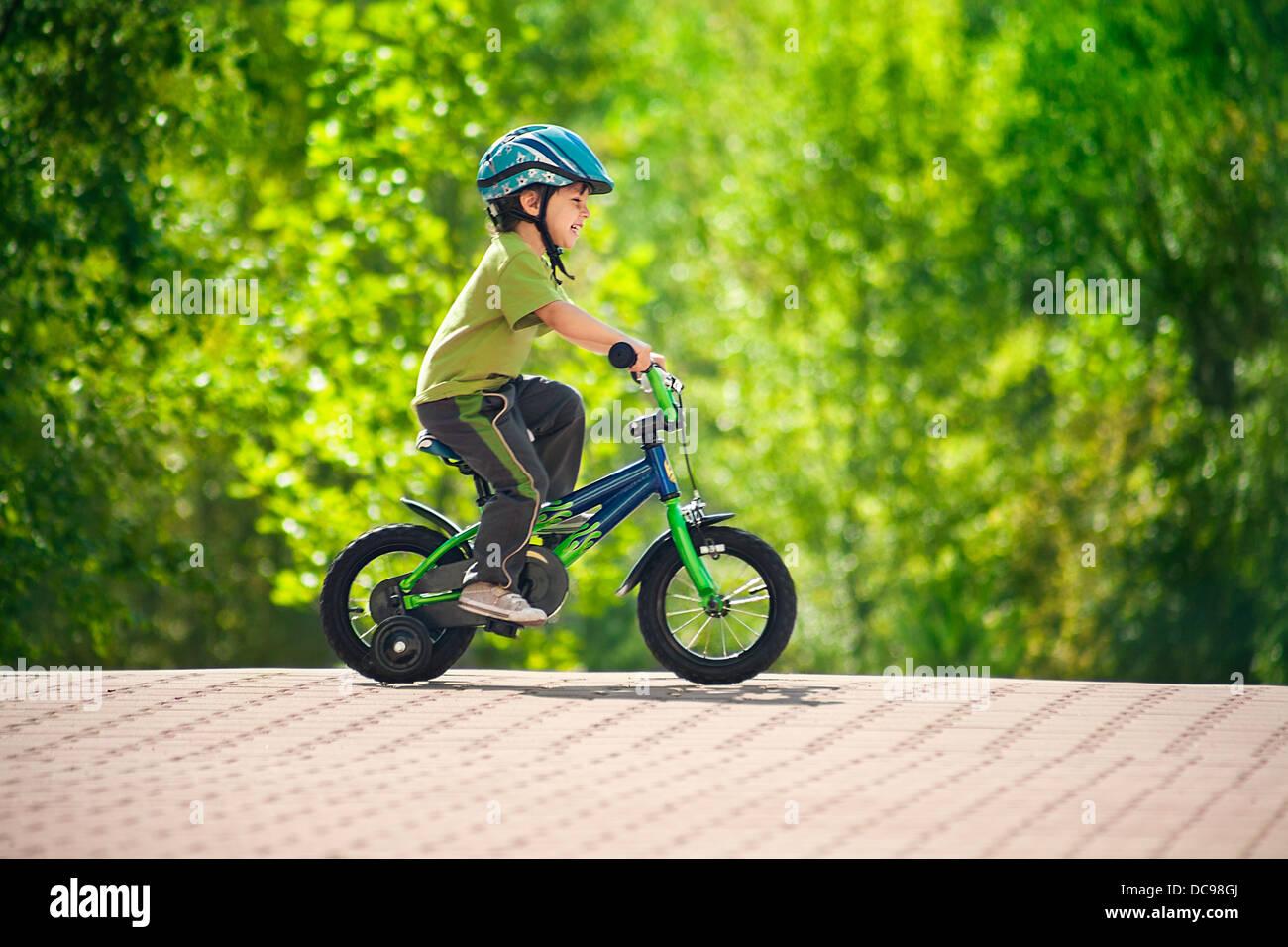 boy in a helmet riding bike - Stock Image