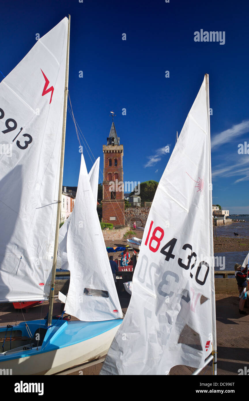 Launching sailing dinghies with Peters Tower in background, Lympstone Harbour, Exe Estuary, Devon, UK - Stock Image
