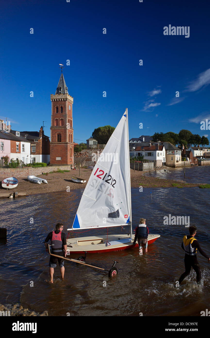 Launching a sailing dinghy with Peters Tower in background, Lympstone Harbour, Exe Estuary, Devon, UK - Stock Image
