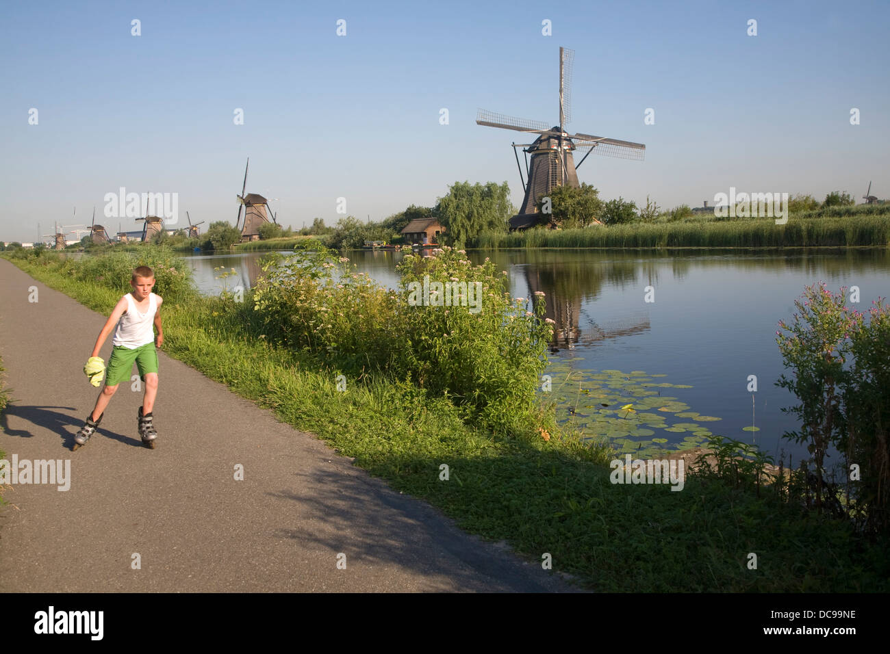 Traditional Dutch windmills Kinderdijk Netherlands boy roller skating on path Stock Photo
