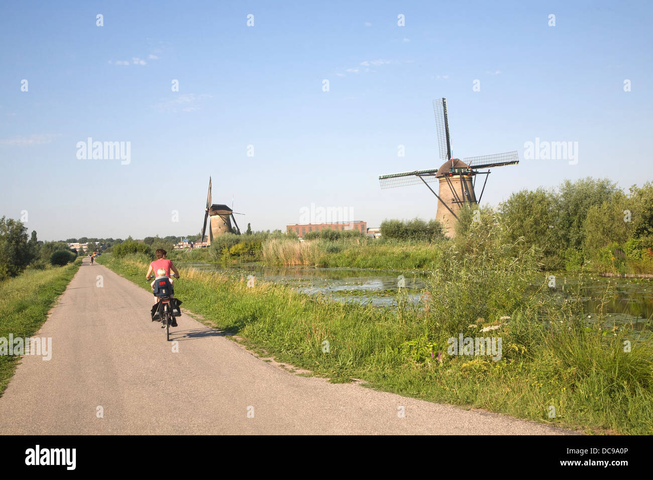 Traditional Dutch windmills Kinderdijk Netherlands cyclist on path Stock Photo