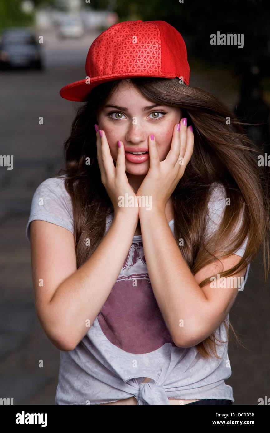 surprised beautiful emotional teen model on street. red cap, grey t-shirt, dark blue shorts - Stock Image