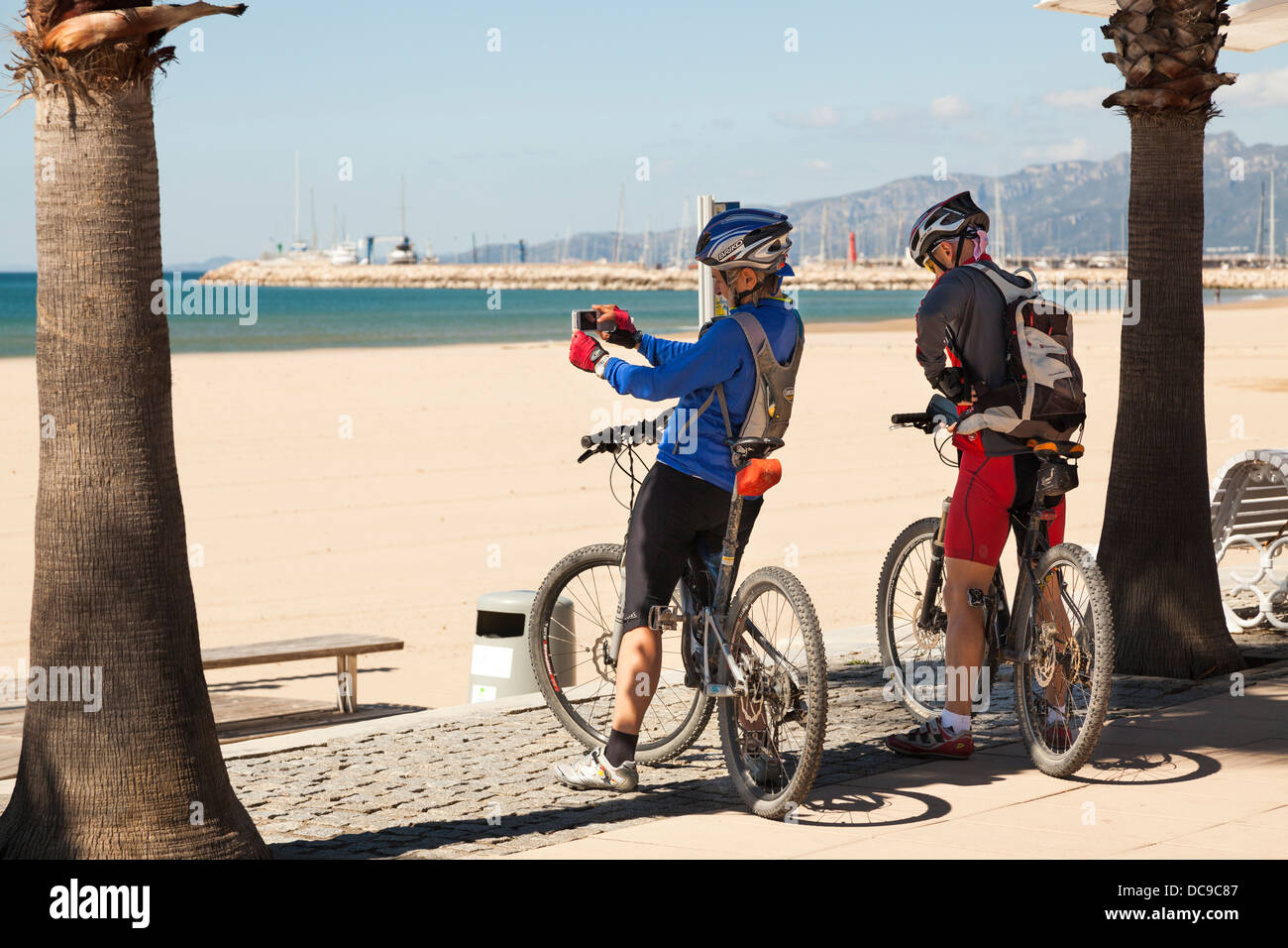 two cyclists photographing seafront at Cambrils on mobile phones - Stock Image