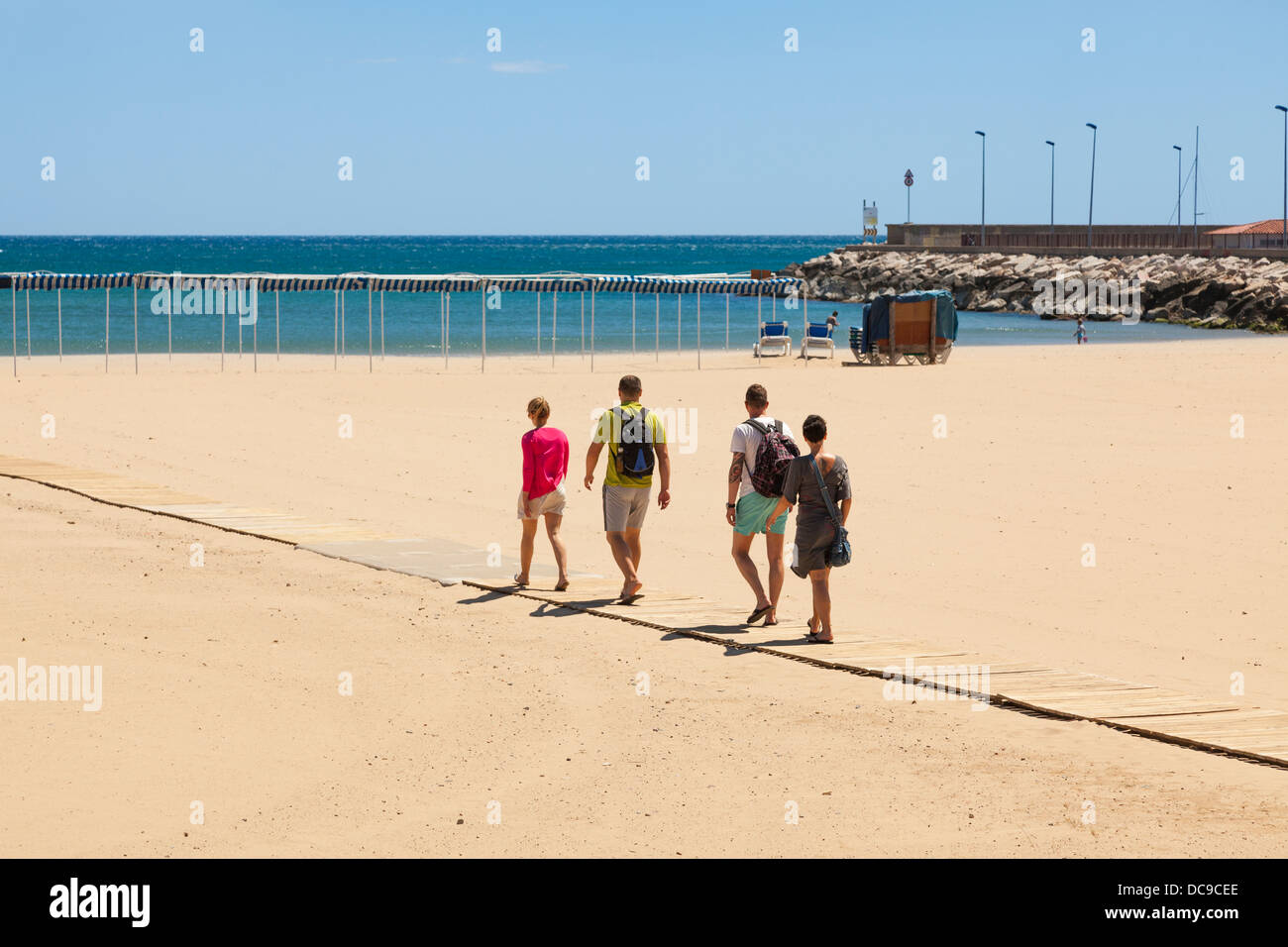 Four people walking down slatted wood access ramp to beach at Cambrils< Spain. Stock Photo