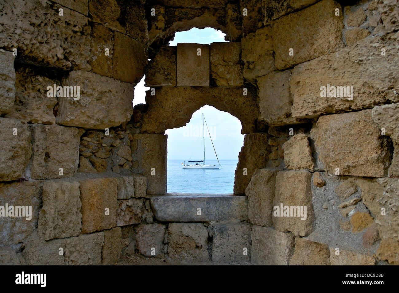 A ship flying german flag, through the walls of the medieval city of Rhodes. Greece. - Stock Image