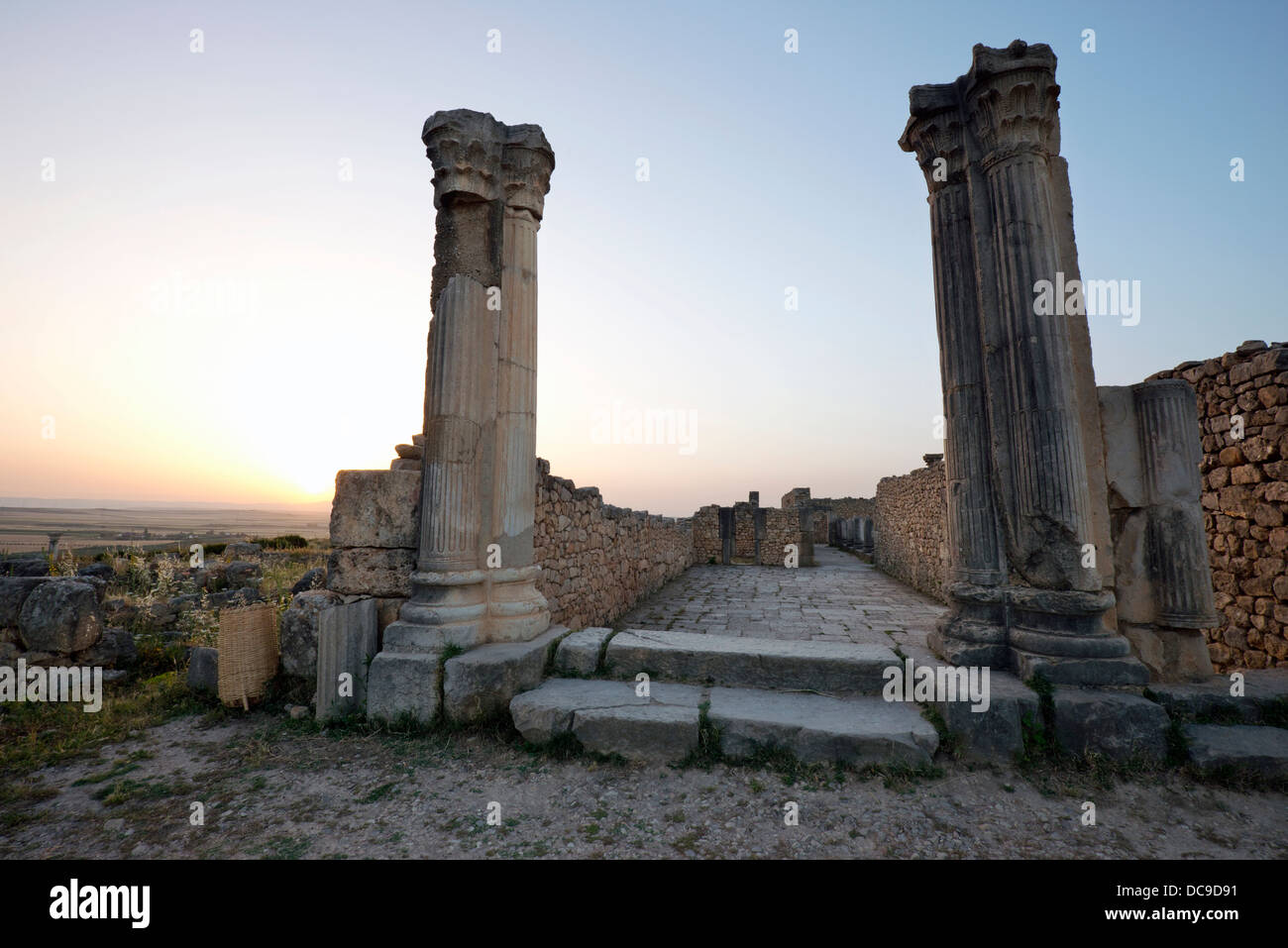 Ancient Roman ruins at sunset at the partially excavated Roman city of Volubilis near Meknes, Morocco. - Stock Image