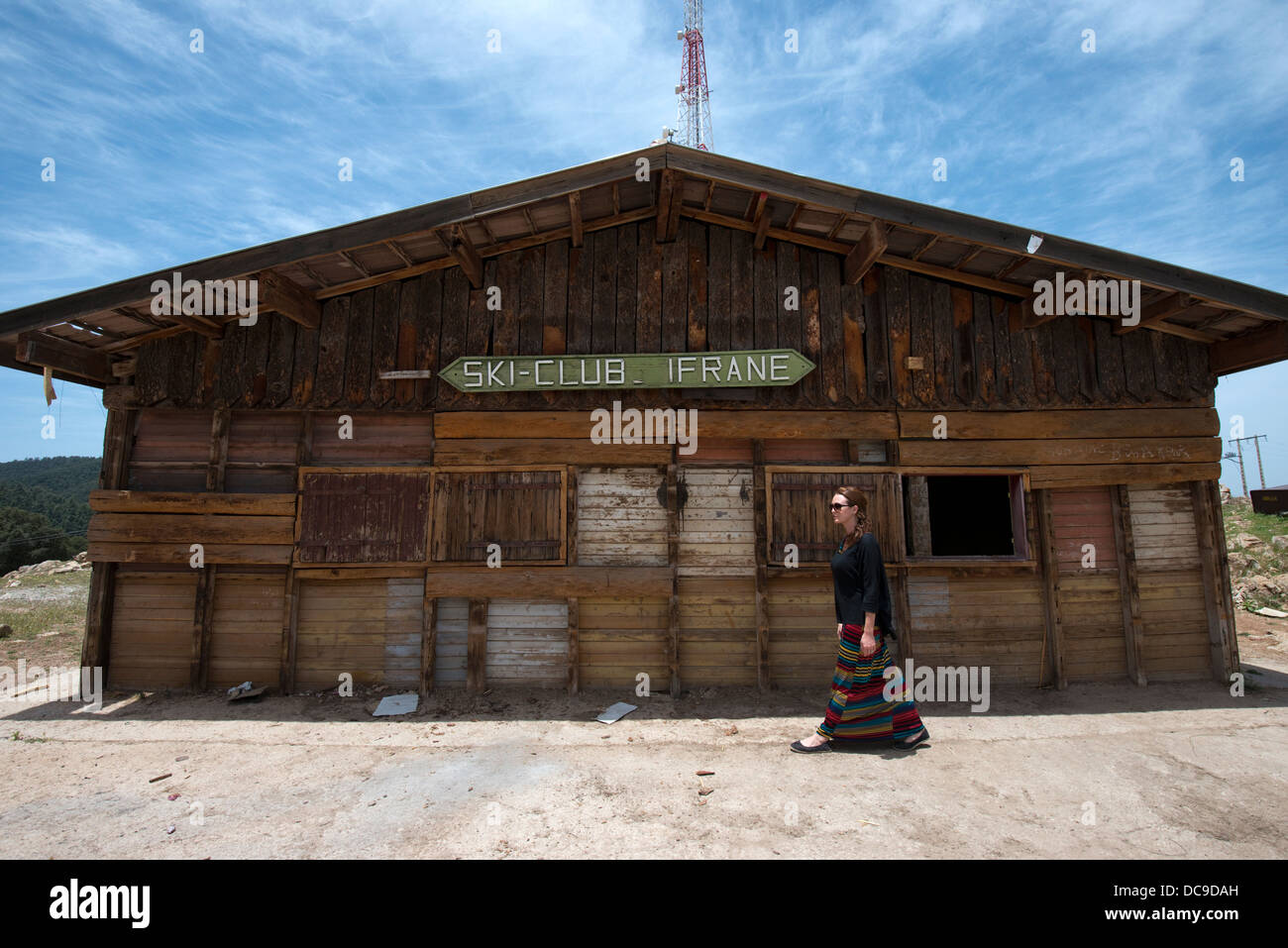 A woman walks in front of the old ticket office at the Ifrane Ski Club in Ifrane, Morocco. - Stock Image