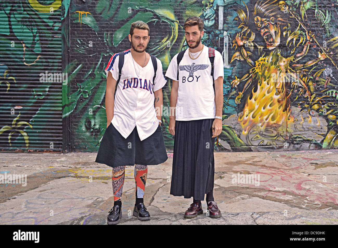 2 young men in skirts, photographed against a graffiti background at 5 Pointz in Long Island City, Queens, New York - Stock Image