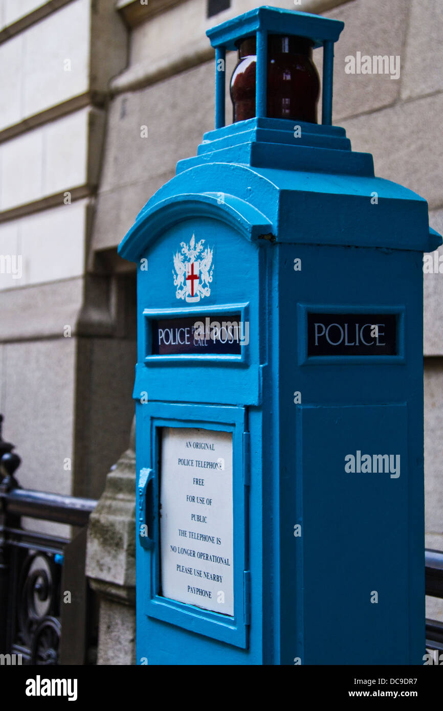 Old style blue public telephone box to call the police in the City of London - Stock Image