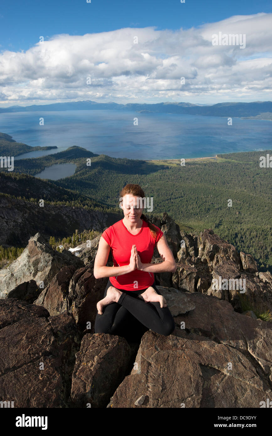 A woman performs yoga on top of Mount Tallac overlooking Lake Tahoe on a beautiful afternoon near South Lake Tahoe, - Stock Image