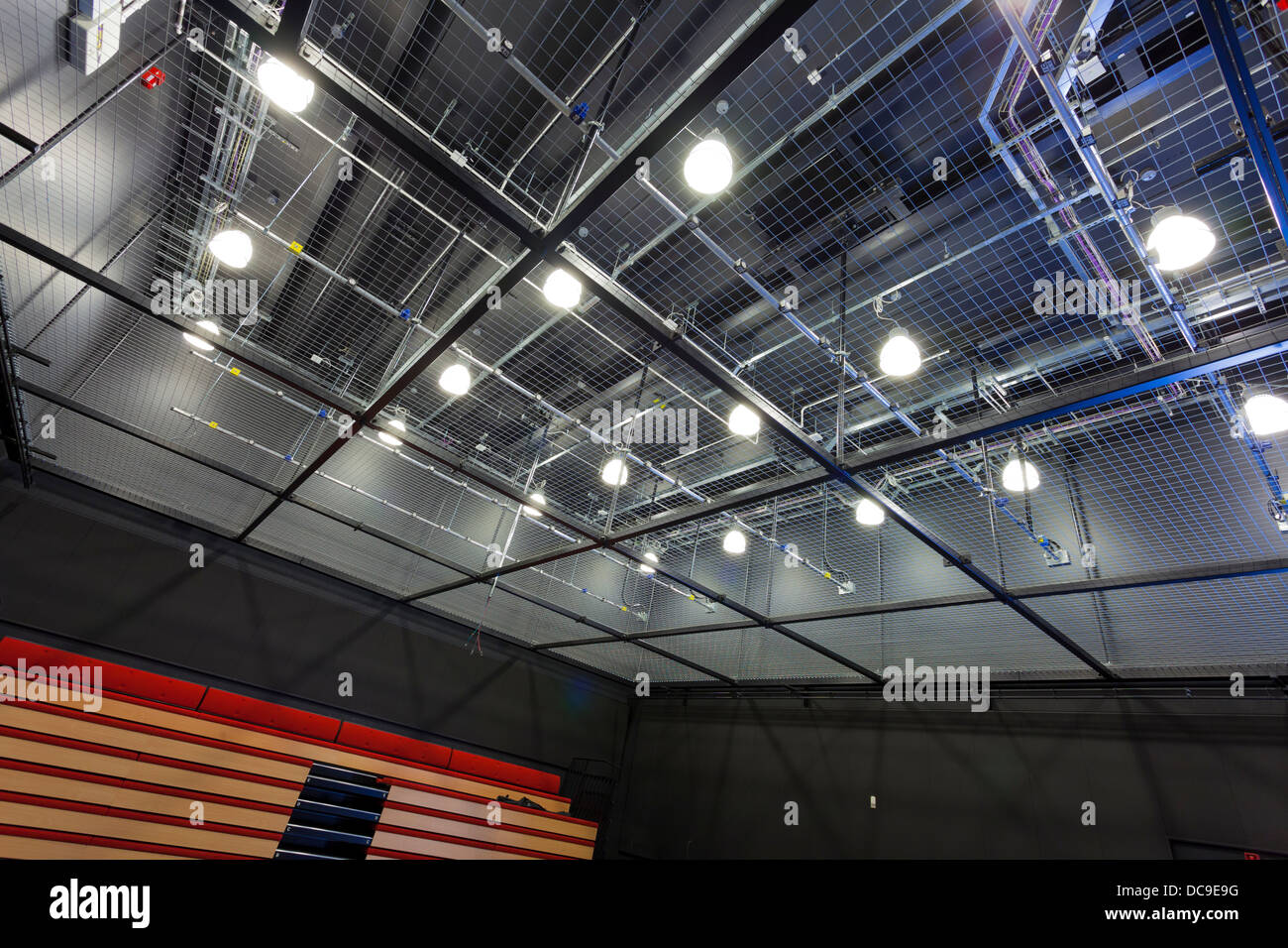 mesh mezzanine floor to access lighting rig in school theatre - Stock Image