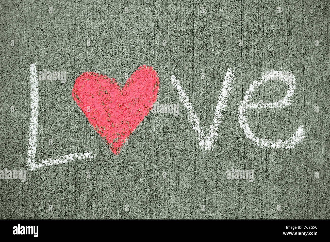 the word love is written in white chalk on a sidewalk, and has a pink heart for the letter o. - Stock Image