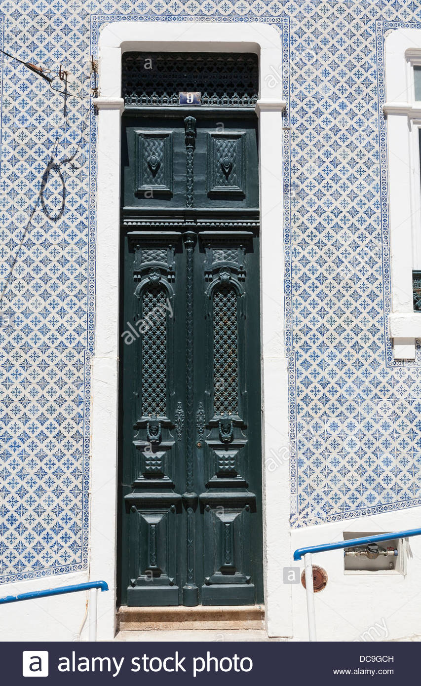 A tall narrow pair of old doors to a Portuguese house. The house is covered in decorative blue and white tiles called azulejo & A tall narrow pair of old doors to a Portuguese house. The house is ...