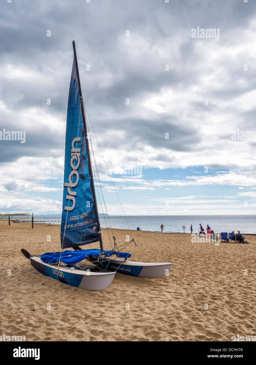 A catamaran with a blue sail on the beach next to the English Channel at Boscombe, Bournemouth, Dorset Stock Photo