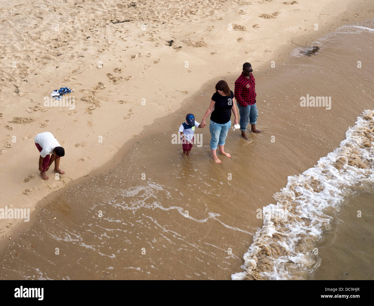A family paddling and enjoying the sea and sand at Boscombe, Bournemouth, Dorset - Stock Image