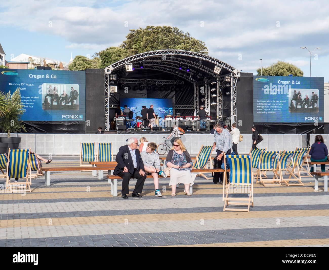 People sit on deckchairs at the bandstand,  the centre of live music concerts Bournemouth, Dorset - Stock Image