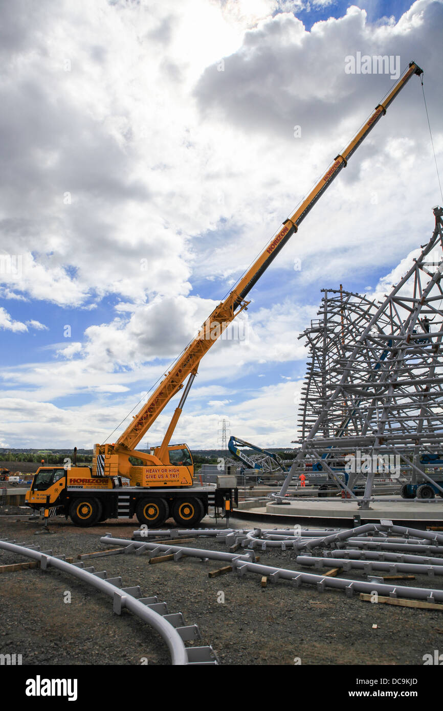 A mobile crane on a construction site hoisting steelwork on to a structure. - Stock Image