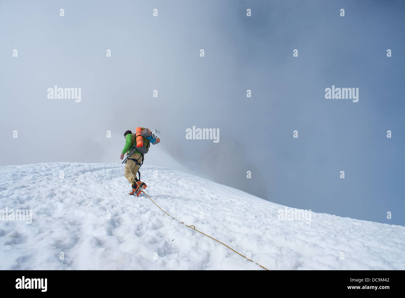 Low view on alpinist during alpine ascent to Aiguille du Midi cable car station from Vallee Blanche in clowdy conditions. - Stock Image